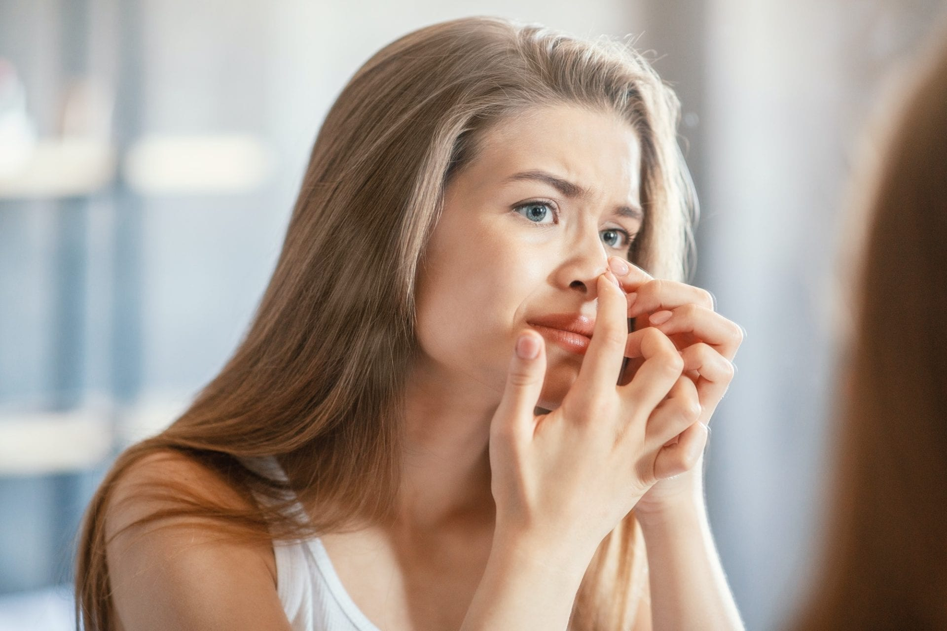 Displeased young woman squeezing acne on her nose while looking in mirror indoors