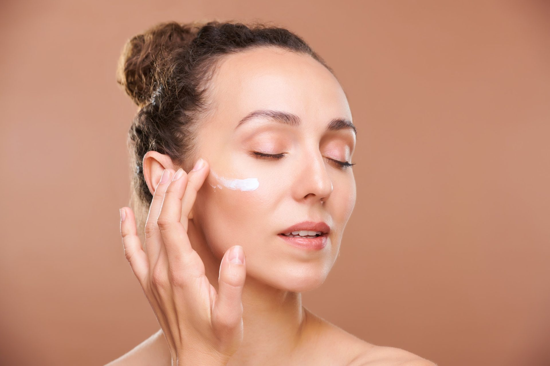 Young gorgeous woman applying facial cream or serum on undereye area